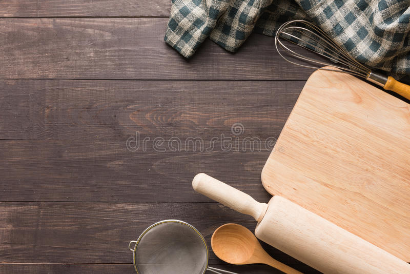Wooden kitchen tools and napkin on the wooden background.  stock images