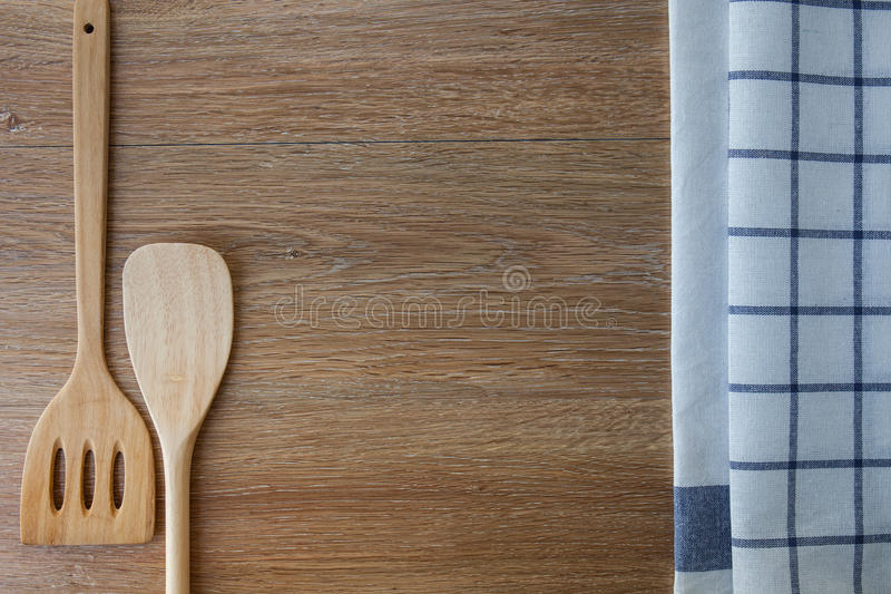 Wooden kitchen utensils and linen kitchen towels on wood table stock images