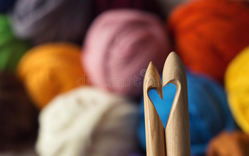 Wooden knitting needles on background of colorful merino wool ba. Lls, heart symbol royalty free stock photography
