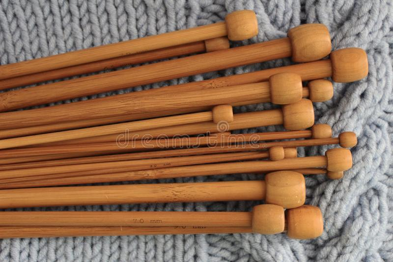 Wooden knitting needles on blue knitted background. royalty free stock image