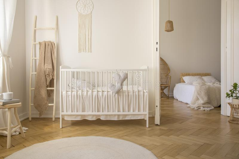 Wooden ladder with beige blanket white crib real photo. Wooden ladder with beige blanket on it, next to white crib with pillows, real photo stock photos