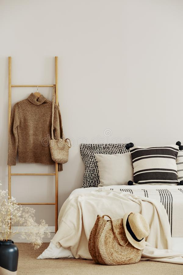 Wooden ladder with sweater and bag next to bed with striped bedding stock images