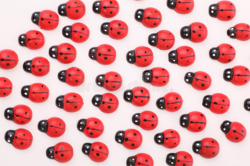 Wooden ladybugs. Lots of wooden ladybugs looking in one direction stock photography