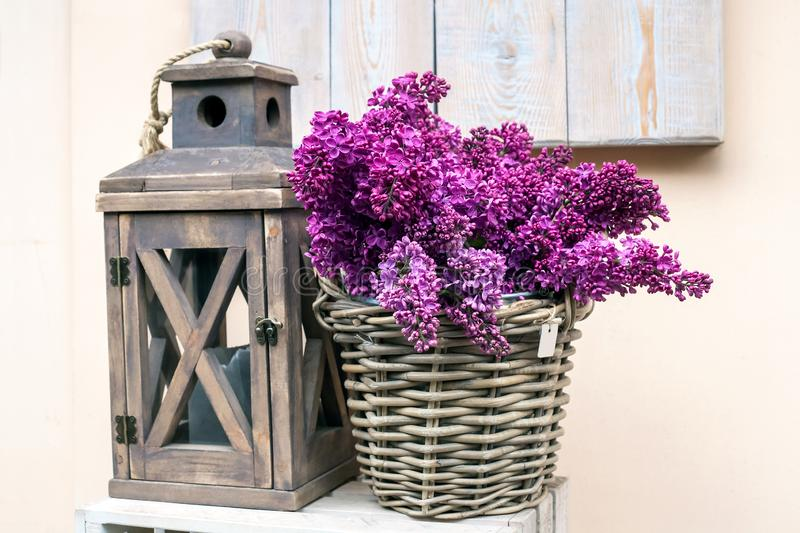 Wooden lamp and bouquet of purple lilac. On woods table, home decor stock image