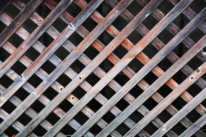 Wooden lattice with a regular pattern. Old and weathered wooden lattice pattern with the background with a regular pattern stock photo
