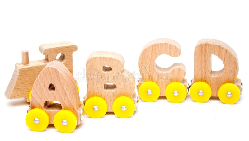 Wooden Letters A, B, C, D of a train alphabet and locomotive with yellow wheels on white background. Early childhood education, le. Arning to read, preschool and stock photography