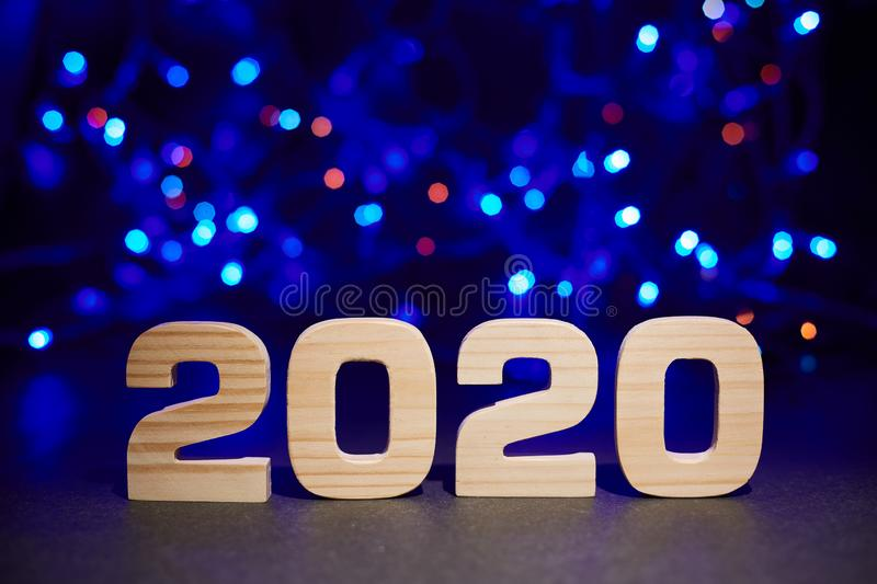 2020 wooden letters on a background of blue bokeh lights. Christmas or New Year card royalty free stock image