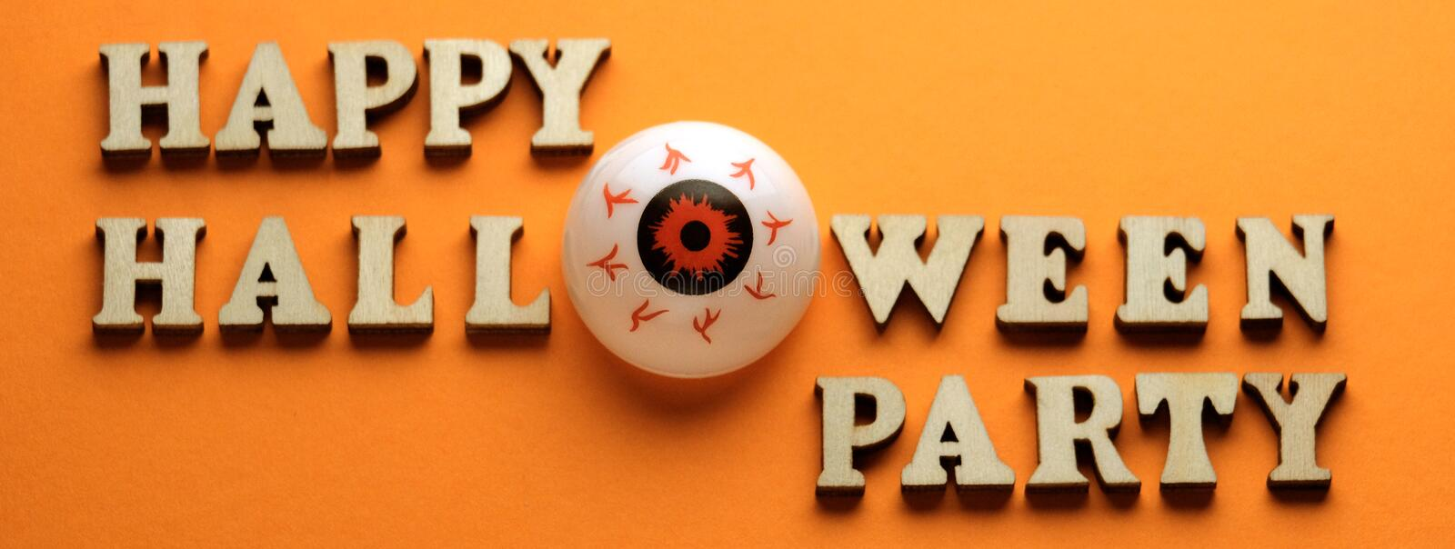Wooden letters on a bright orange background. Eye instead of the letter O on a stylish inscription HAPPY HALLOWEEN PARTY. Template. Wooden letters on a bright royalty free stock photos