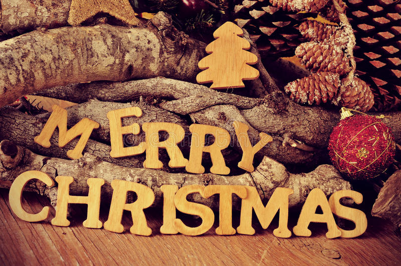 Wooden Letters Forming The Sentence Merry Christmas On A Rustic Table With Logs And Pine Cones In Background