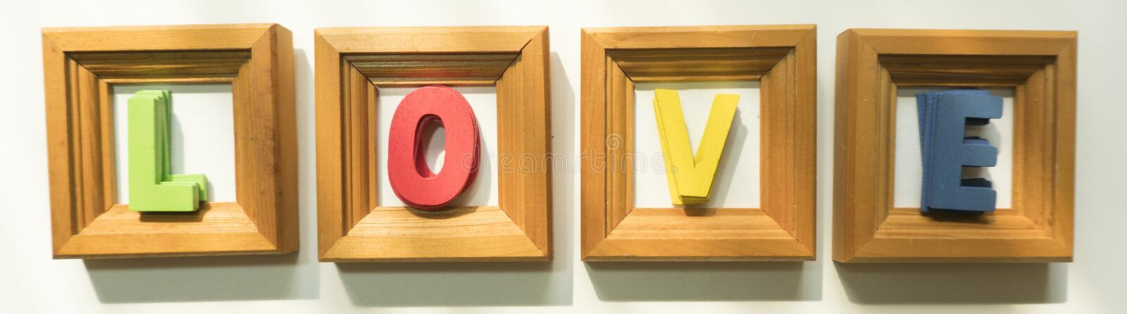 The wooden letters of green, red, yellow, and blue were written 'love' in the square frame stock photos