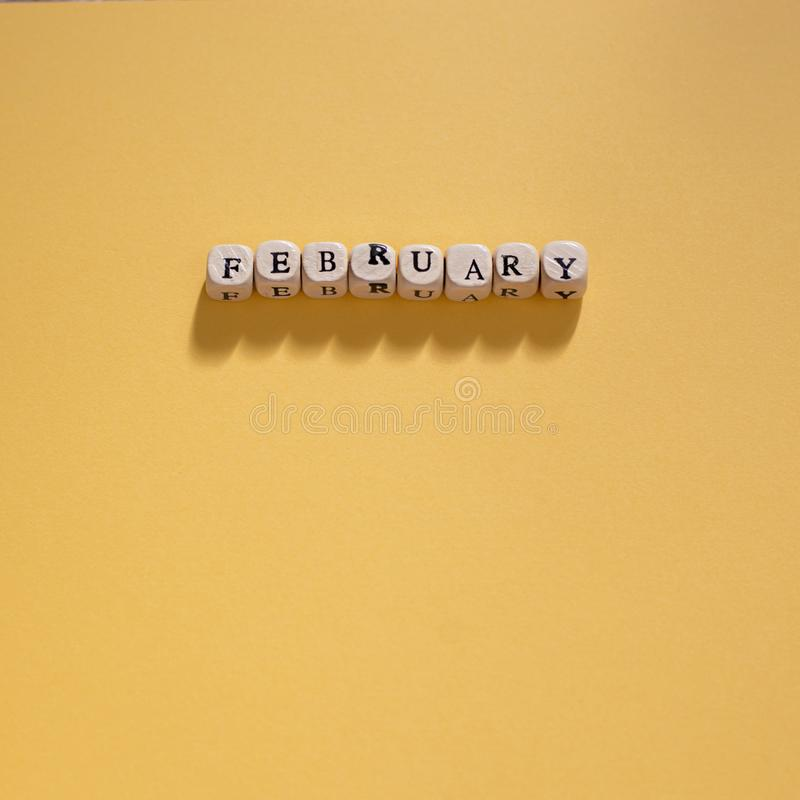 Wooden letters spelling February on a yellow background. Photograph of wooden letter tiles / beads spelling February on a yellow background on a square royalty free stock images