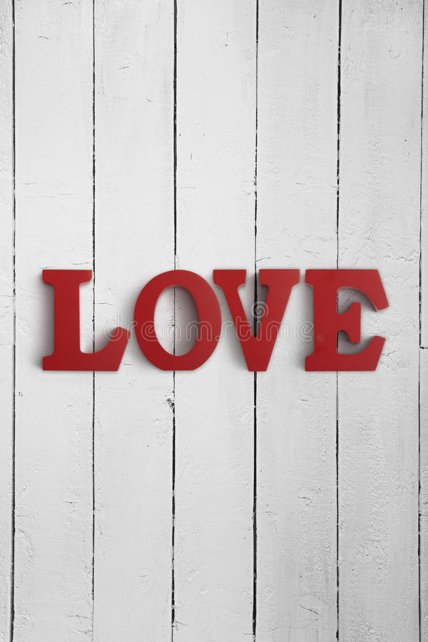 Wooden letters spelling LOVE. On a wood background stock photography
