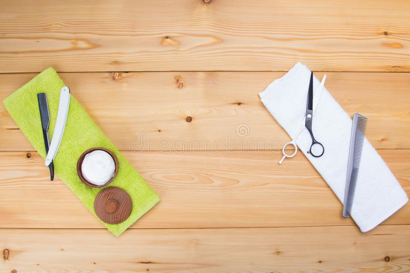 Wooden light background are 2 towels, green and white, which are objects for cutting beard and hair razor, comb and scissors. On a wooden light background are 2 royalty free stock image