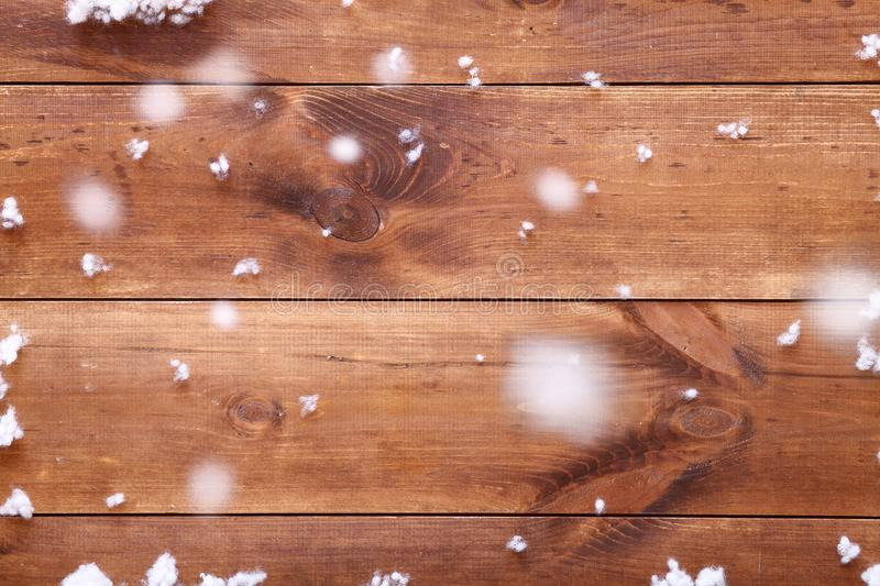Wooden brown background table with white snowflakes, empty blank wood board and falling snow, top view, copy space stock images