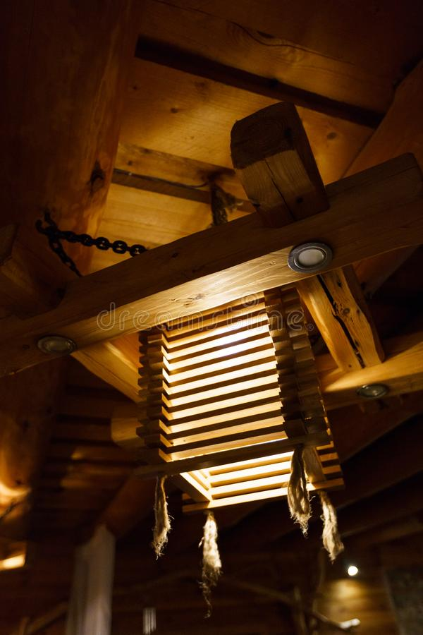 Wooden light chandelier at a ceiling LAtvia royalty free stock images