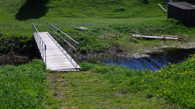 Wooden little bridge across the creek. Natural stock image