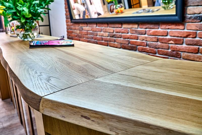 Wooden live edge table in solid oak. Solid oak countertop. Live edge counter top. Details furniture. Solid oak reception royalty free stock photography