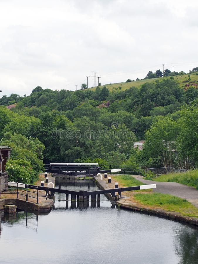Wooden lock gates on the calder and hebble navigation canal in front of the basin in sowerby bridge west yorkshire surrounded by. Trees and buildings, towpath royalty free stock photos