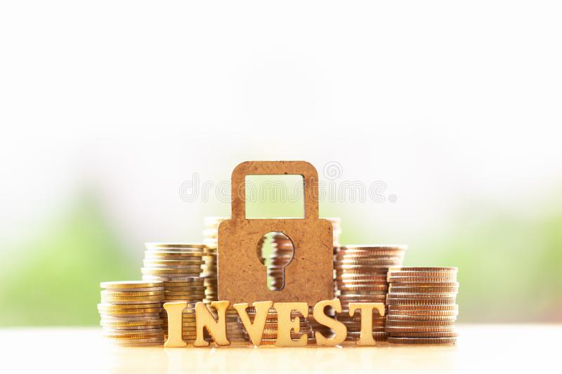 Wooden lock and stack of coins in concept of savings and money growing or energy save. stock images