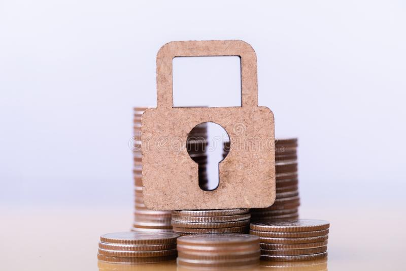 Wooden lock and stack of coins. royalty free stock photos