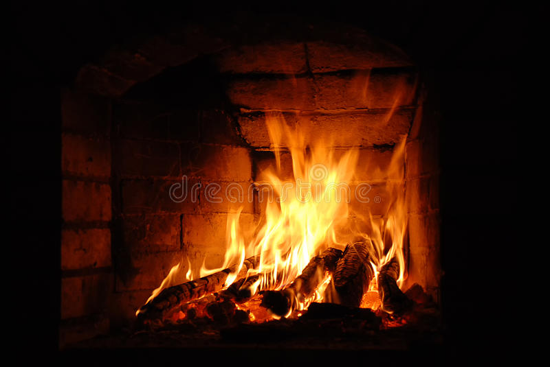Wooden logs burning brick fireplace stock photos