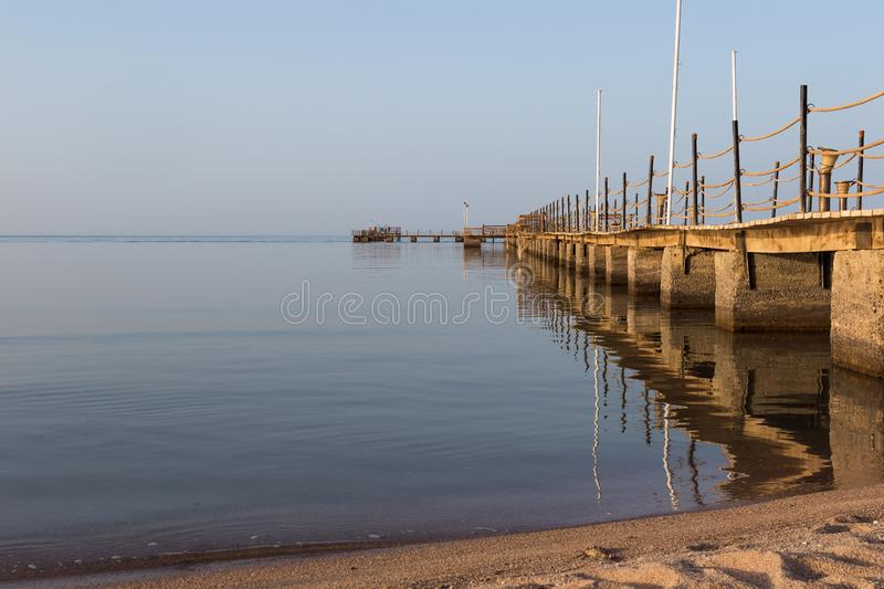 Wooden long old pier with reflection at sunset on the  background royalty free stock photo
