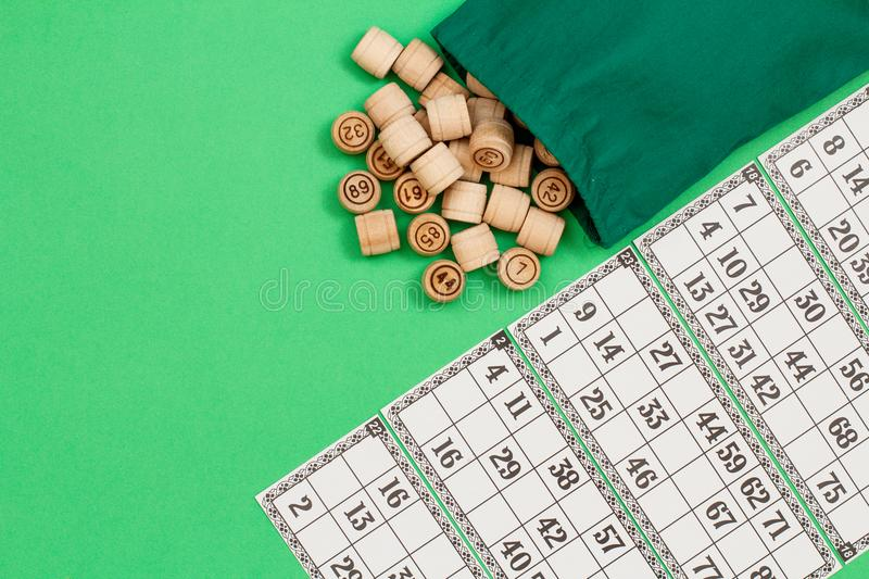 Wooden lotto barrels with bag and game cards on beige background stock photos