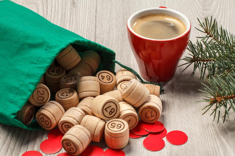 Wooden lotto barrels with bag, game cards, red chips, cup of coffee and Christmas fir tree branches stock photography