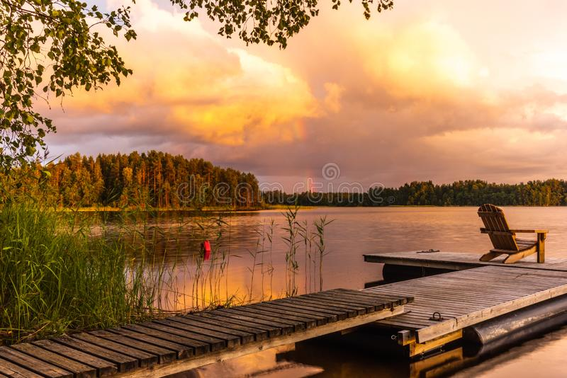 Wooden lounge chairs at Sunset on a pier on the shores of the calm Saimaa lake in Finland under a nordic sky with a rainbow. Wooden lounge chairs at Sunset on a royalty free stock photography