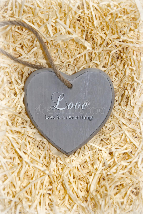 Wooden love heart in saying love is a sweet thing. Single grey wooden love heart in a love nest made of straw inscribed love is a sweet thing royalty free stock image