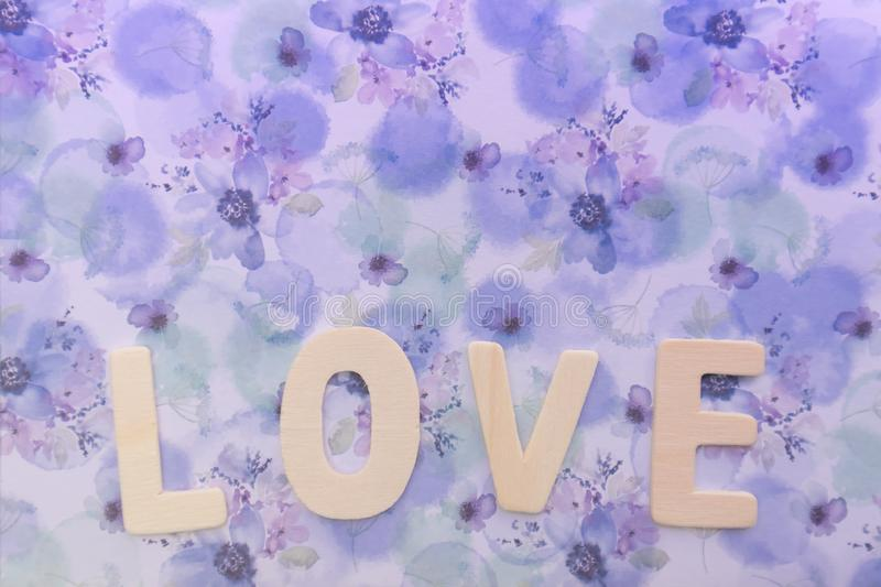 Wooden love letter on the violet floral gift wrapped paper as background with copy space royalty free stock photo