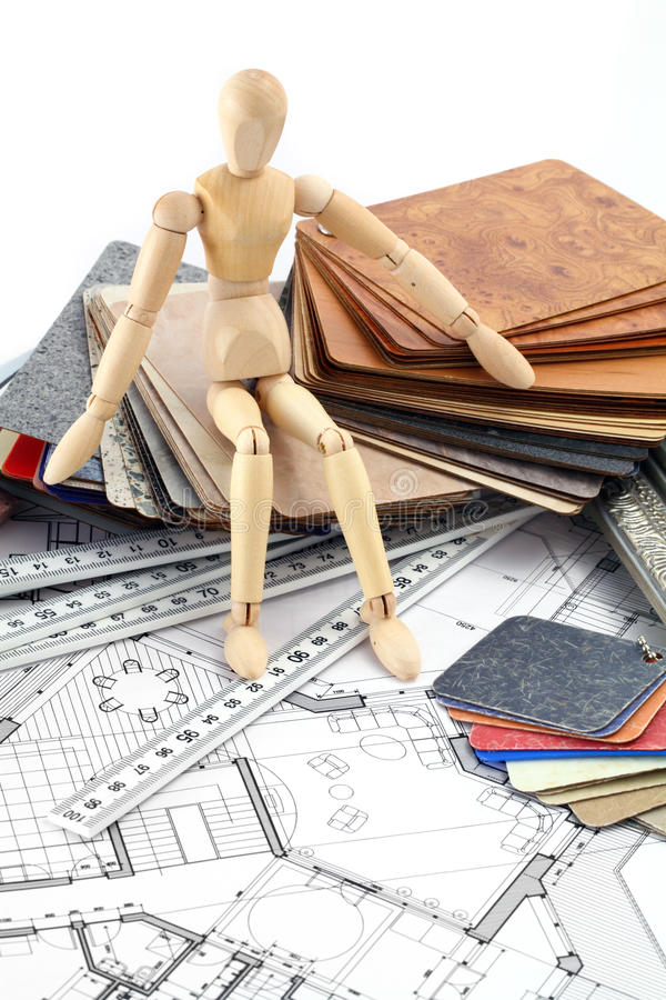 Wooden man, furnishing materials, blueprints. Wooden man, color samples of architectural materials - plastics, Metric Folding ruler and architectural drawings of royalty free stock photo