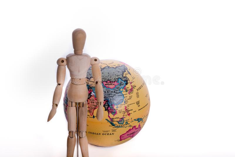 Wooden man and globe. Wooden man standing in front of a globe on a white background royalty free stock images