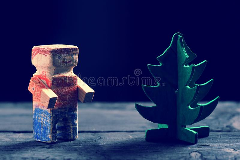 Wooden man and wooden green Christmas tree. On dark background royalty free stock images