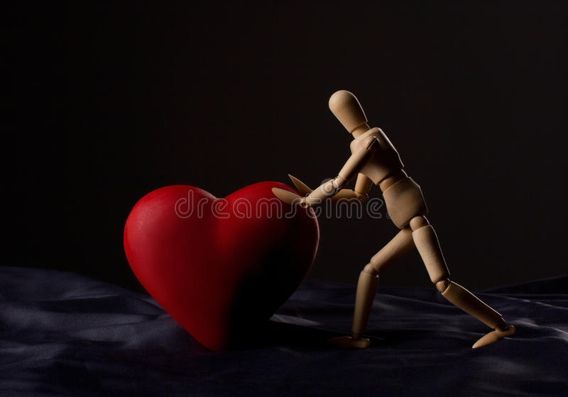 Wooden man and heart. Wooden man pushing a red heart on dark on black background royalty free stock images
