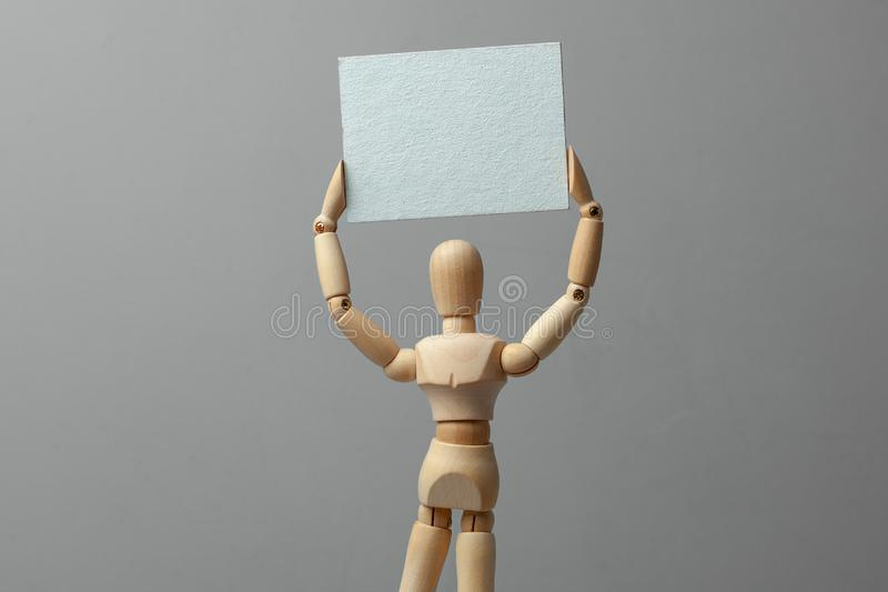 Wooden man holding blank board poster on gray background. royalty free stock photos