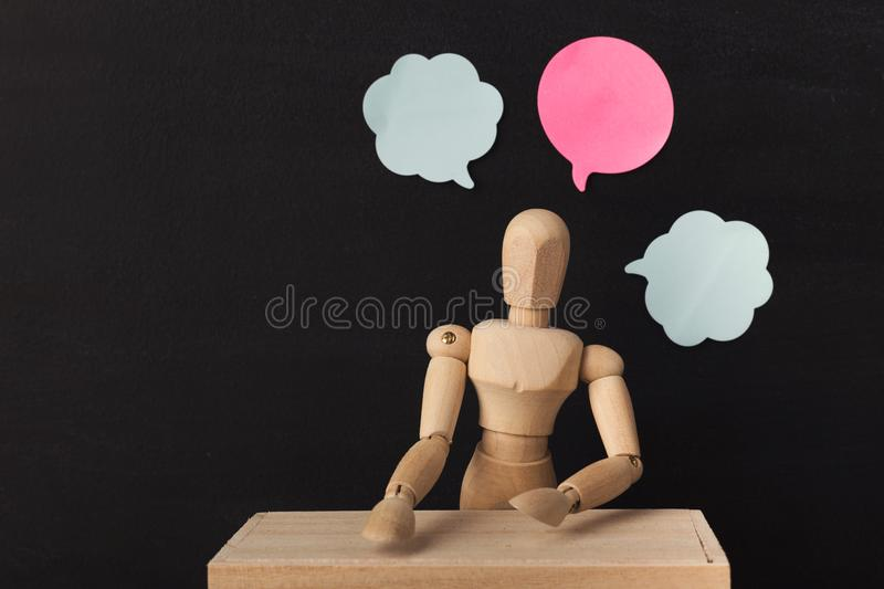 Wooden man mannequin with blank speech bubbles royalty free stock photography