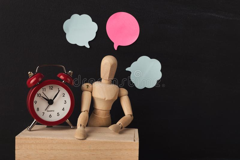 Wooden man mannequin with blank speech bubbles. Wooden man figure mannequinwith blank speech bubbles and alarm clock on black background, objects, nobody royalty free stock photography