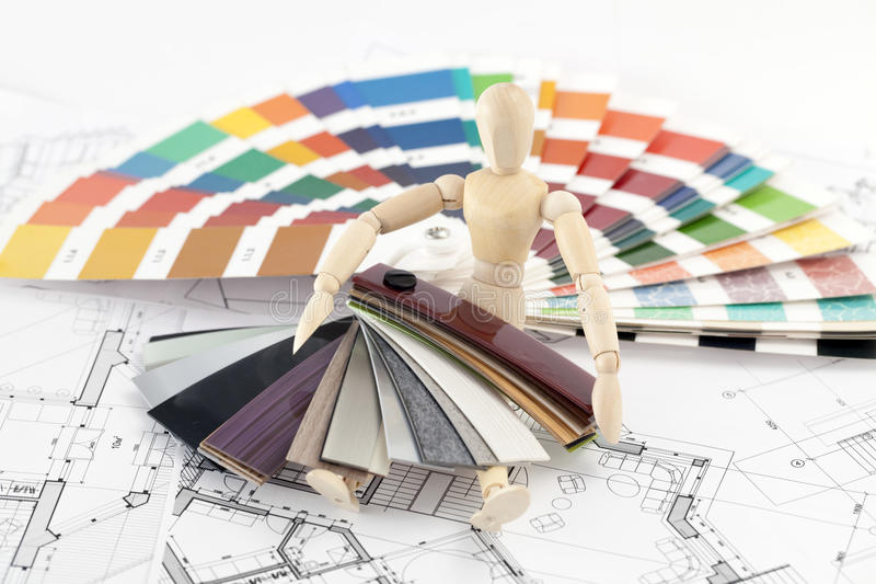 Wooden man and palette of colors. Wooden man, a palette of colors designs for interior works, samples of plastics, PVC, for furnishing and architectural drawings stock photos
