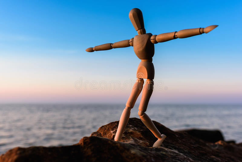 Wooden man at the sea. Wooden man stands on the top of sea boulder royalty free stock photography