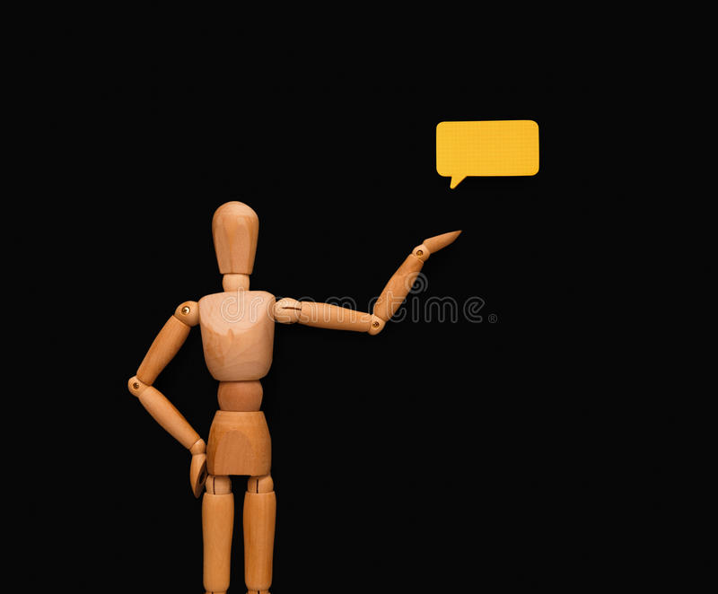 Wooden man with speech bubble, black background royalty free stock photos