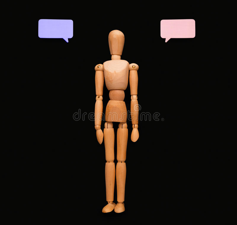 Wooden man with speech bubble, black background stock images