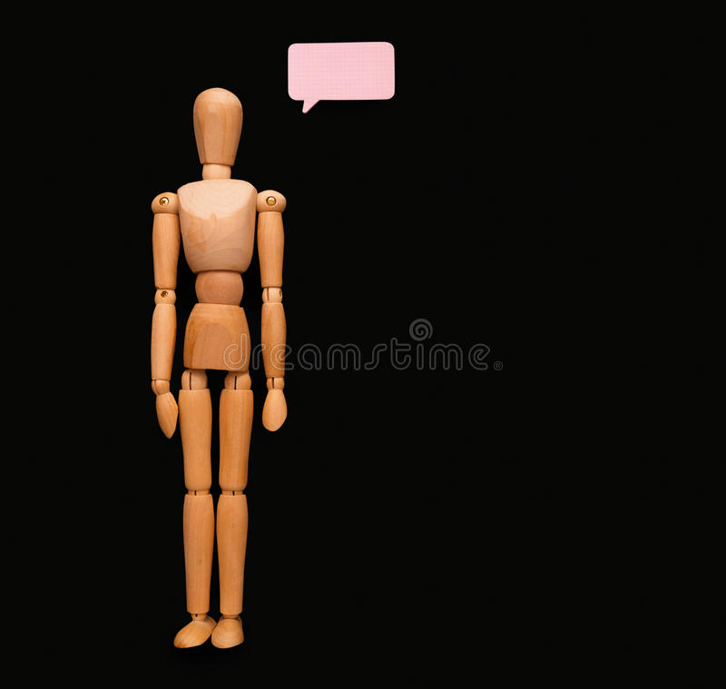 Wooden man with speech bubble, black background stock photos
