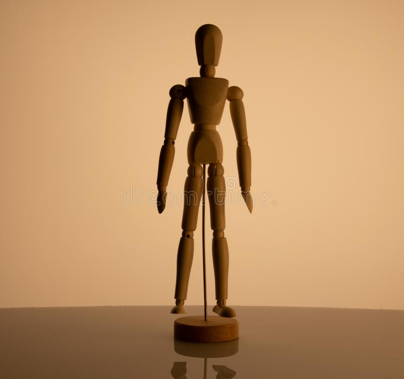 Wooden man toy on beige background royalty free stock photography