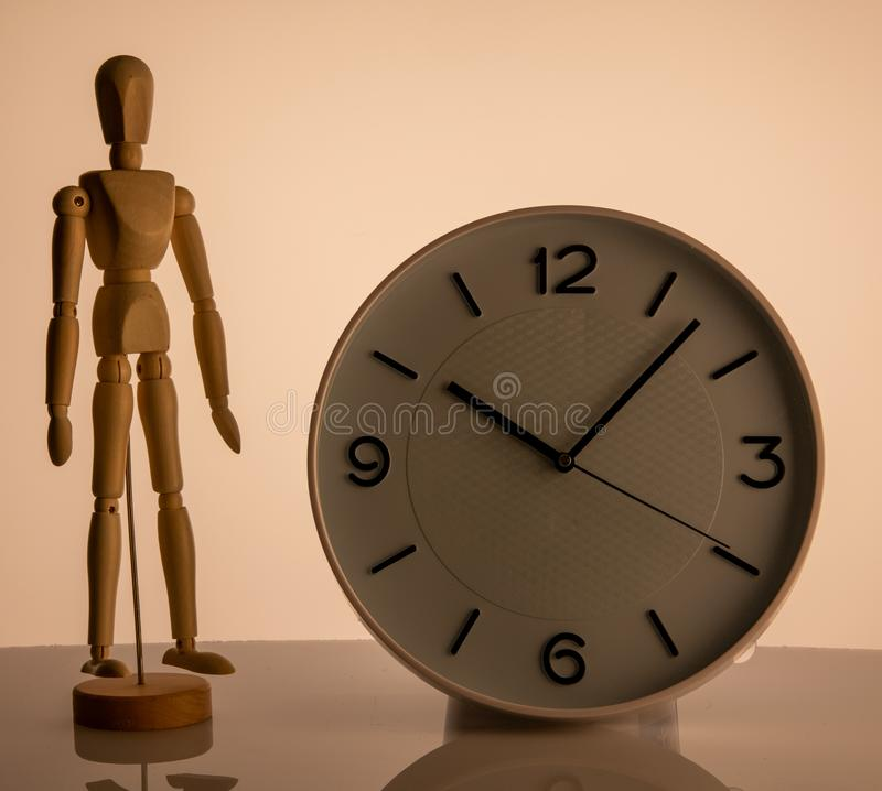 Wooden man toy and clock on beige background royalty free stock photography
