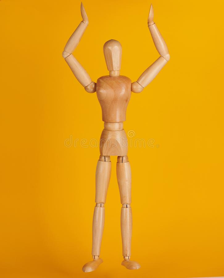 Wooden man toy. With hand up isolated on yellow background royalty free stock photos