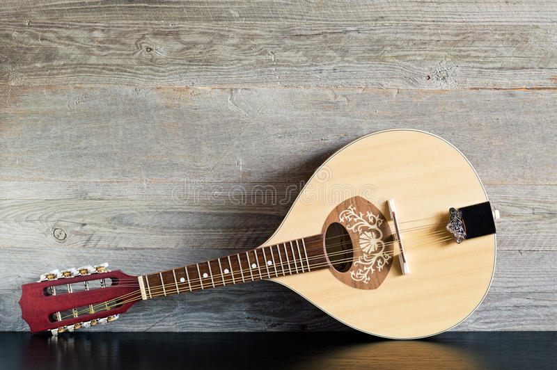 Wooden Mandolin on a Black Table. Front view of a reclined wooden flatback mandolin on a black table with a weathered wood background stock photos