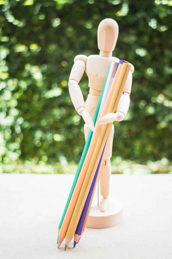Wooden manikin carrying colour pencil on artist work table. Stock photo stock photography