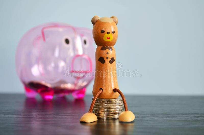 Wooden manikin sitting on coins stock photos