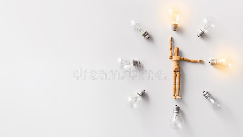 Wooden mannequin carrying glowing light bulbs on white royalty free stock photos